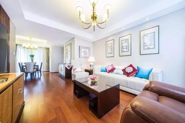 室内满铺深色木地板,电视背景墙为大理石结合部分木